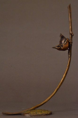 This is a bronze sculpture by Jim Green of a Red-breasted Nuthatch perched on a branch
