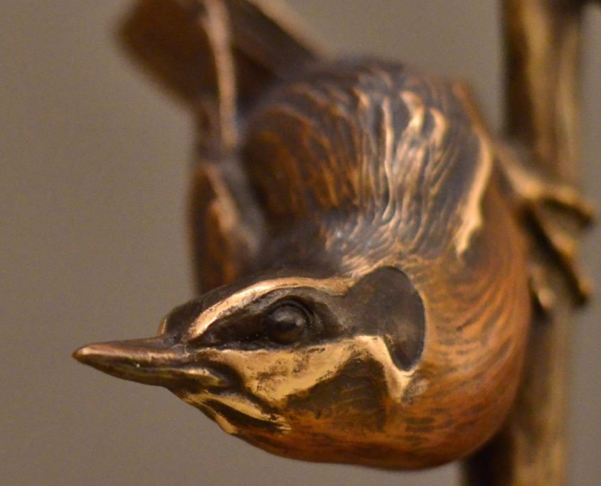 A bronze sculpture by Jim Green of a Red Breasted Nuthatch perched on a branch