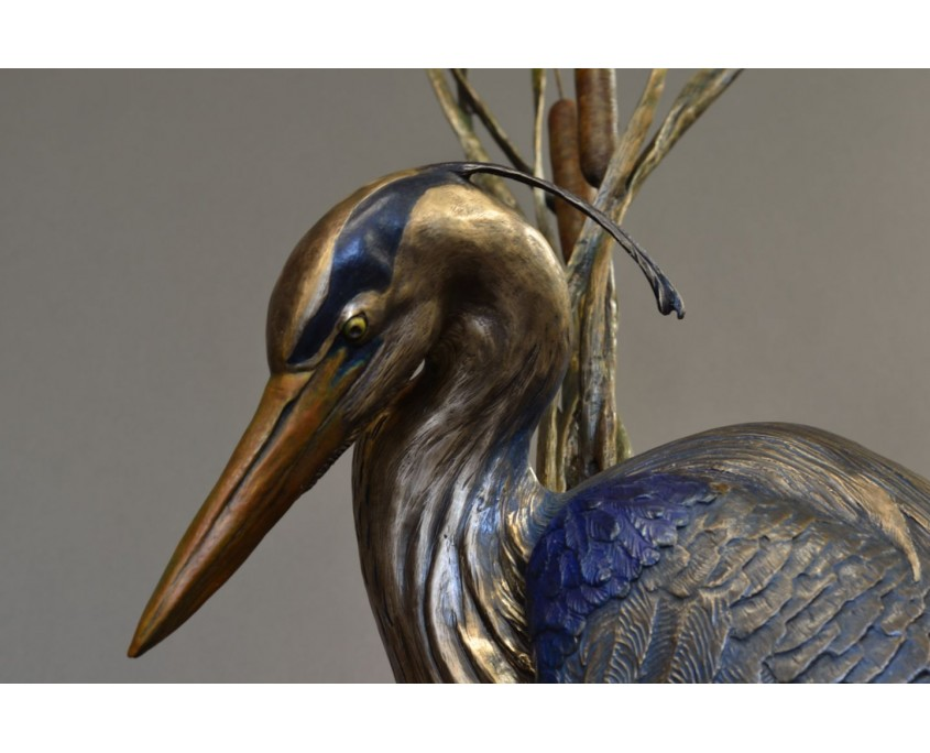 Bronze sculpture by Jim Green of a Great Blue Heron walking in the cattails