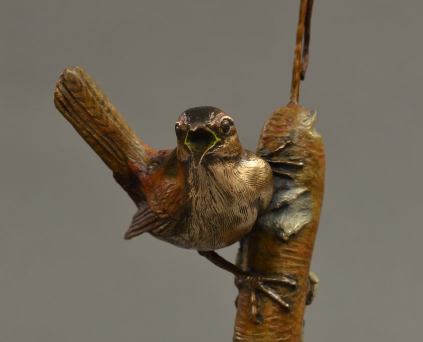 A bronze sculpture of a marsh wren on a cattail by Jim Green