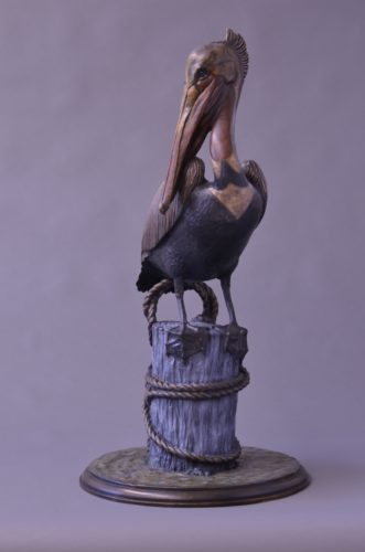 A bronze sculpture of a brown Pelican standing on a pier piling by Jim Green