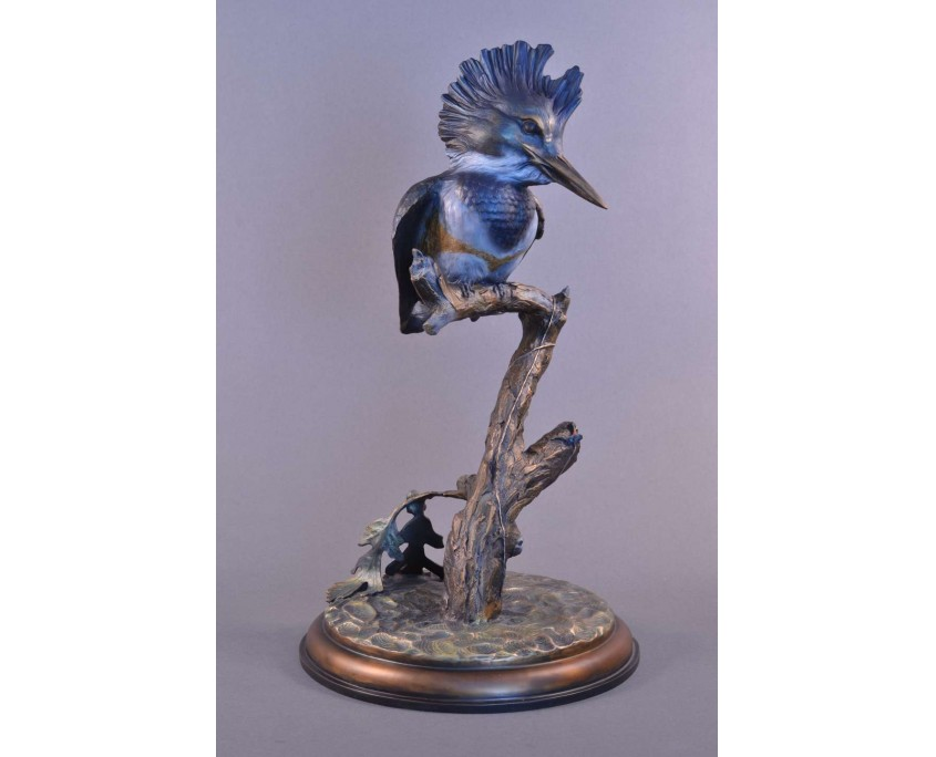 A bronze sculpture by Jim Green of a female King Fisher perched on a branch.