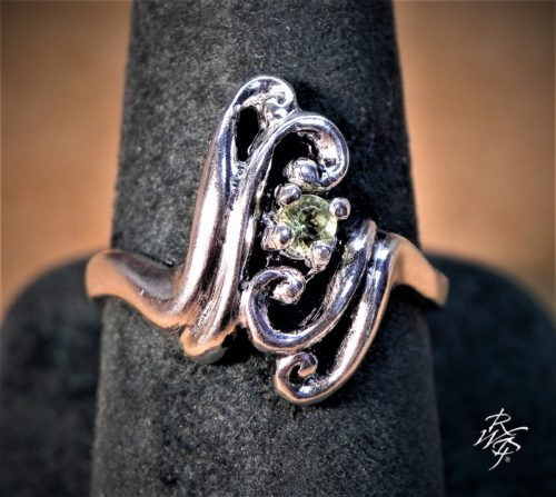 3 mm Peridot set in sterling silver prong setting in a scroll design. Western art inspired design.