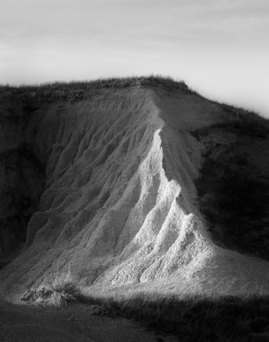 This photo was taken by Amy Lehman in the Badlands of South Dakota. A shaft of setting sun illuminated this badlands bank and highlights the rippling pattern of erosion.